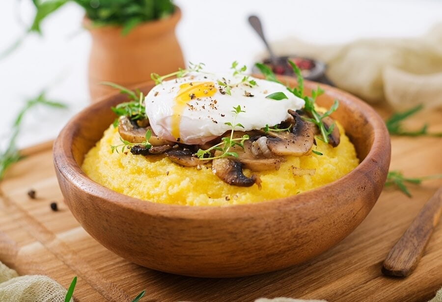 bowl of polenta with a poached egg and sauteed mushrooms