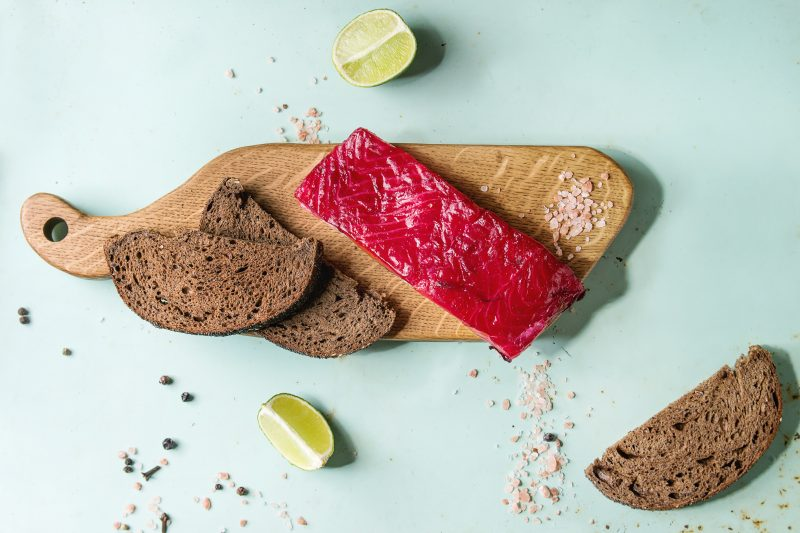 beet brined salmon on wooden board with dark rye bred