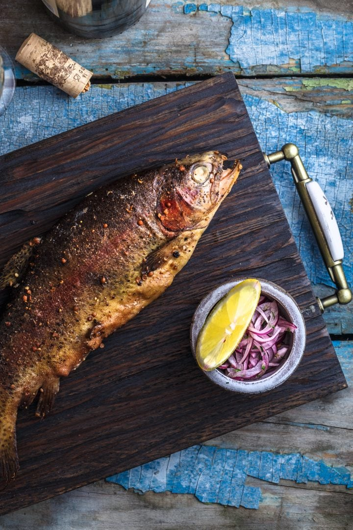 smoked whole trout on tray with coleslaw