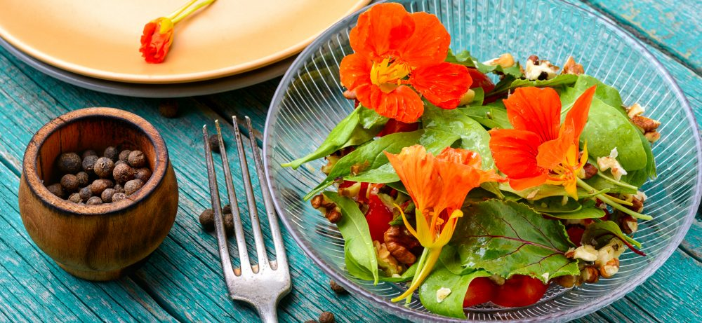 a salad of nasturtium flowers and leaves, walnuts, and a homemade dressing