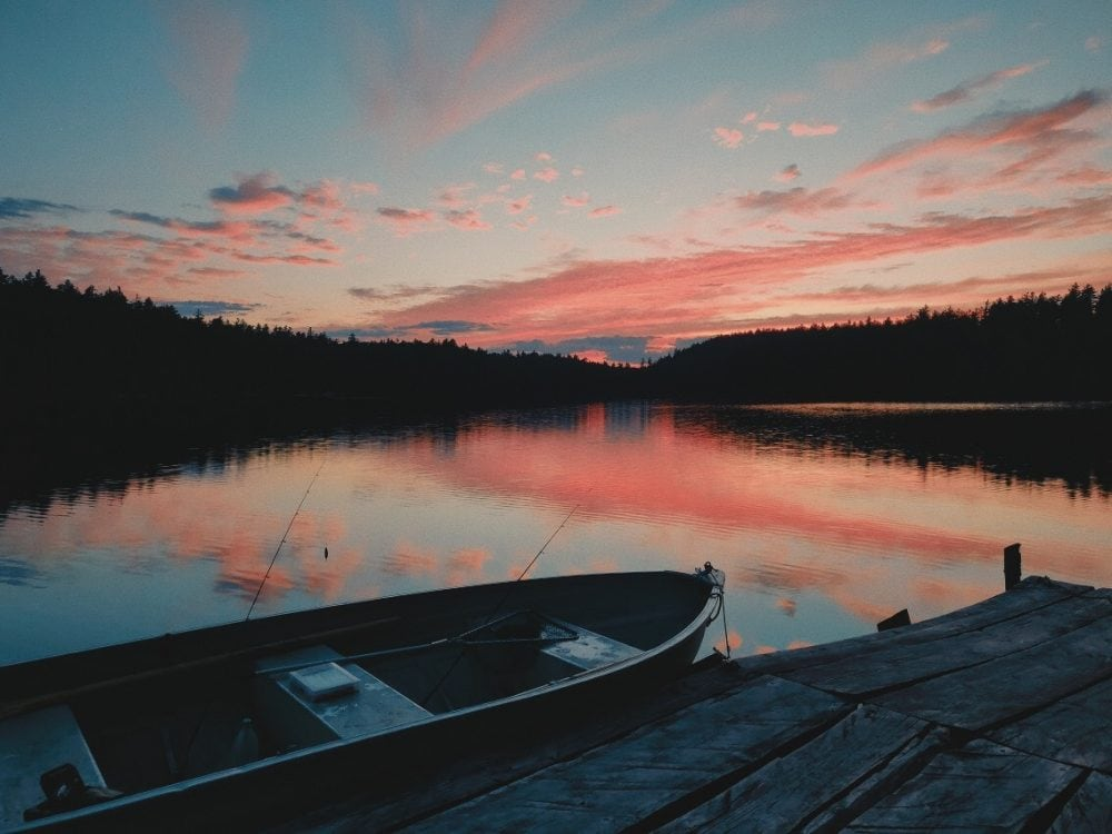 a lake with a dock and boat at sunset
