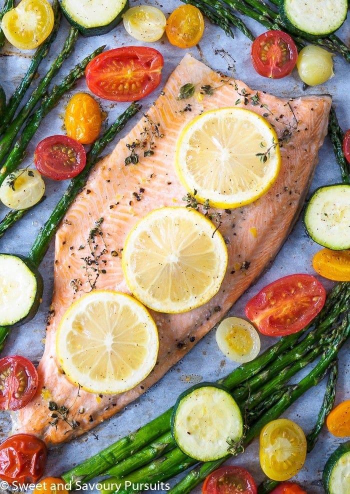rainbow trout fillets and vegetables on a baking sheet