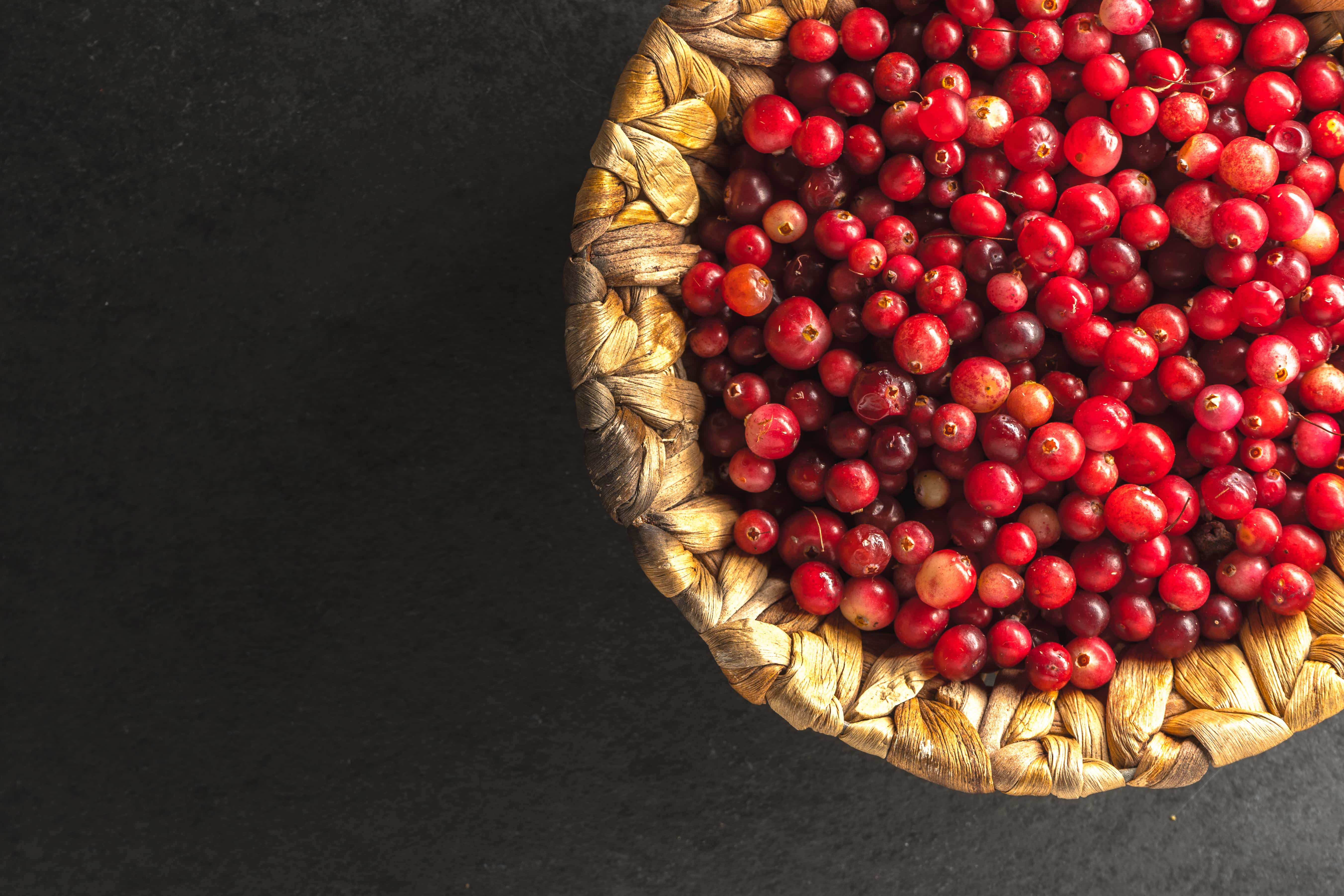 Bright red cranberry in the basket on the right