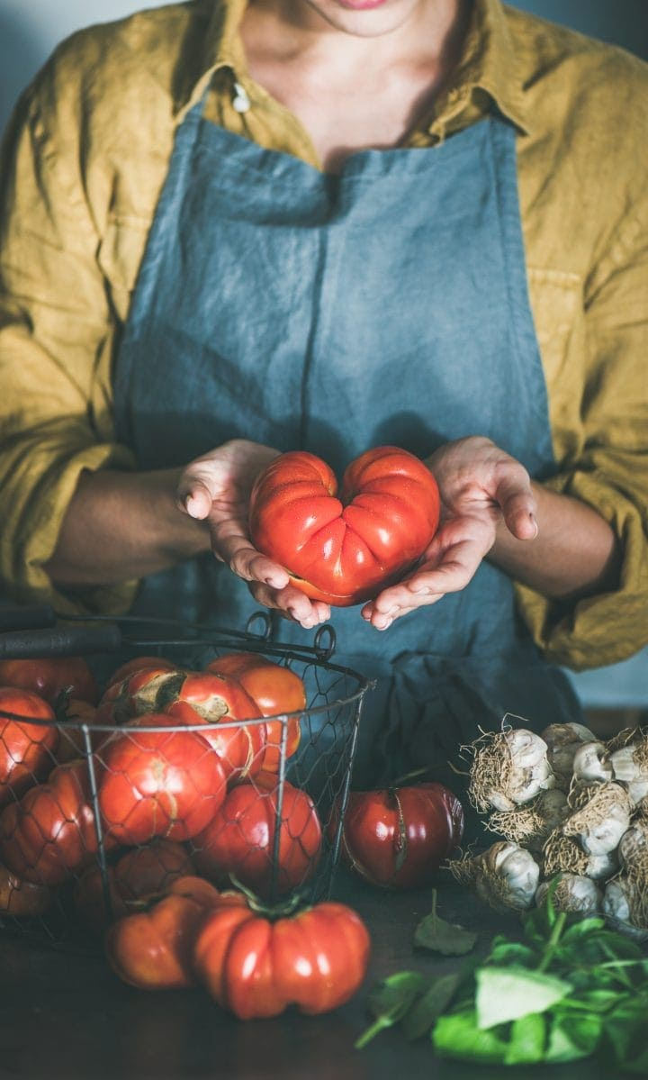 Woman in linen apron holding ripe heirloom tomato for cooking tomato sauce, canned tomatoes or pasta with basil and garlic at kitchen counter. Healthy cooking, slow food or comfort food