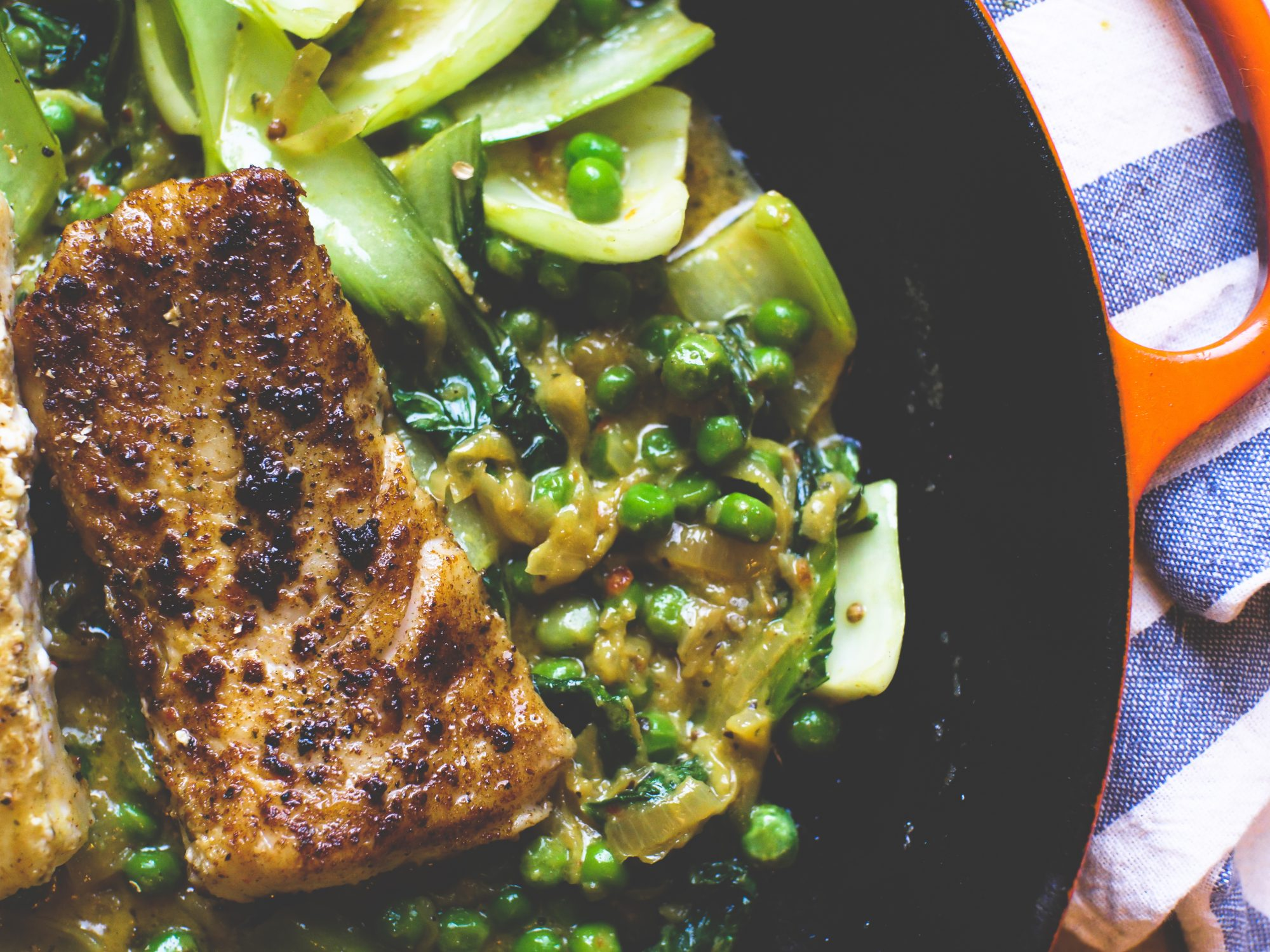 halibut in a creamy turmeric sauce with peas, bok choi, and caramelized onions