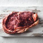 Marbling ribeye steak on white plate
