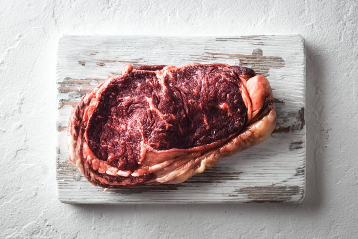 Marbling ribeye steak on white plate