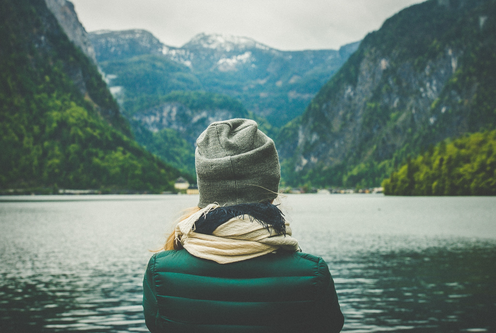a woman looks out at a lake and mountains