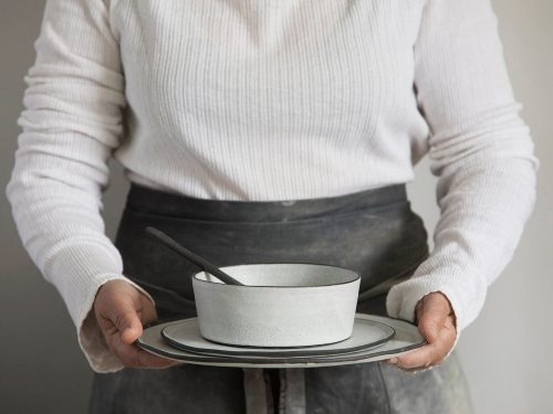 woman holding handmade ceramic dinnerware set