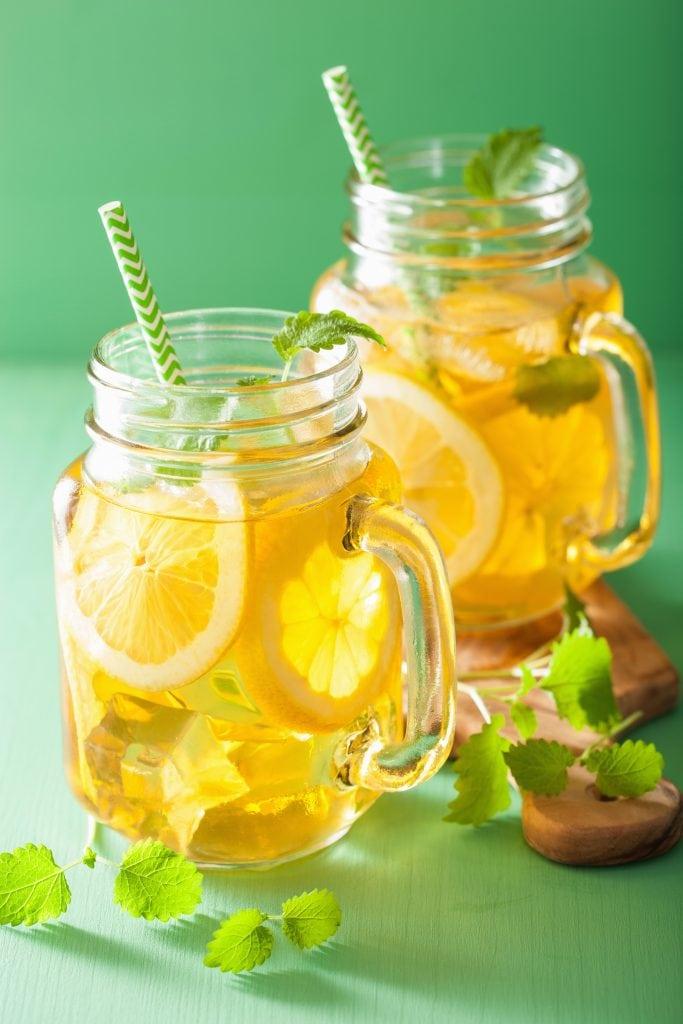 A mason jar with a homemade electrolyte drink mixture and sliced lemons.