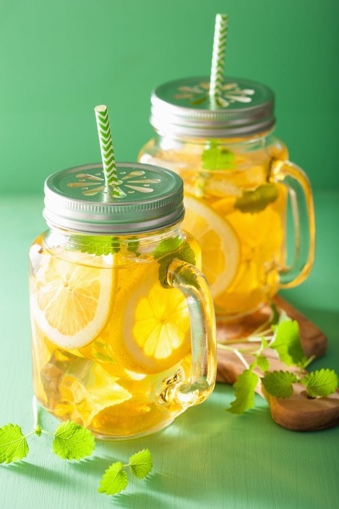 homeade electrolyte drink in covered mason jar with a straw for children