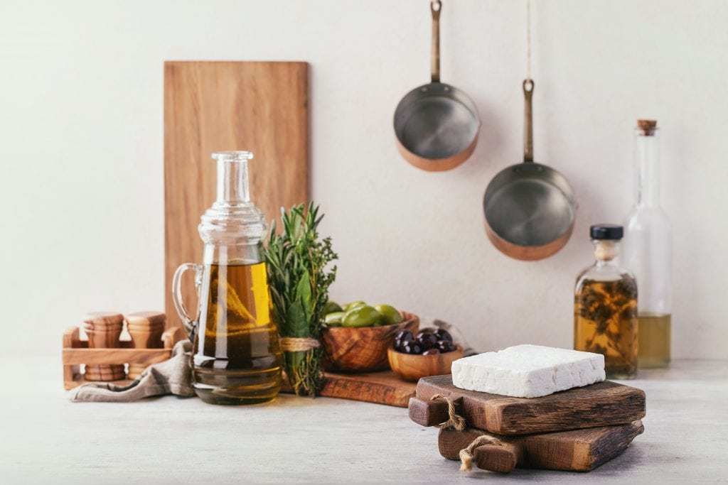 Traditional greek appetizer sheep milk feta cheese served with herbs, green and black olives and extra virgin olive oil.