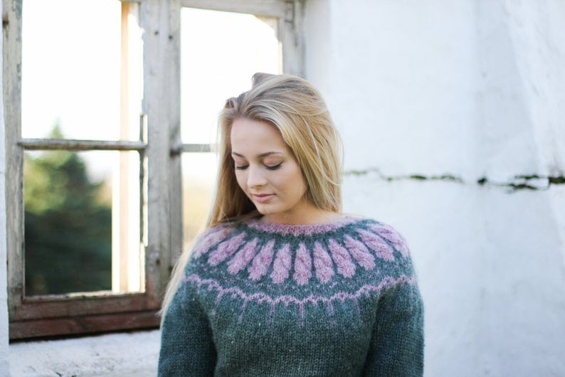 Young blonde woman wearing a traditional Icelandic  sweater in dark grey with purple designs.